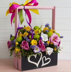Picture of different flowers in wooden box painted with hearts by chalk