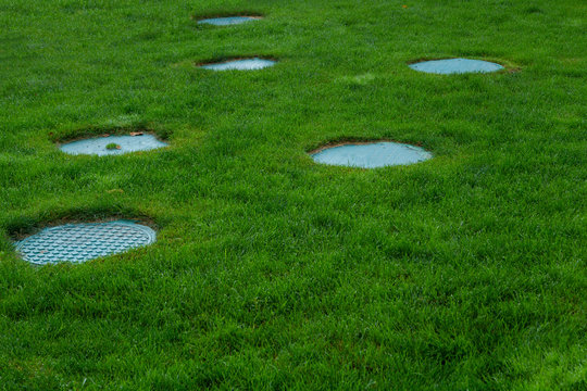 Several covers of sewer hatches on the green lawn. Green lawn with blue sewer hatches. Beautiful decor for sewer hatches.