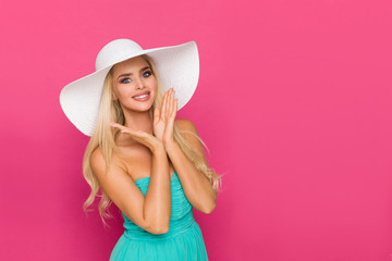 Beautiful Woman In White Sun Hat Is Posing With Head In Hands And Smiling