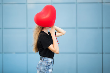 Woman in the street on a blue background. Red heart shaped ball. Valentine's Day