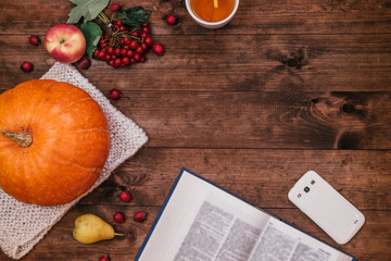 Top view of a  pumpkin, apples and a book, phone on wooden table.