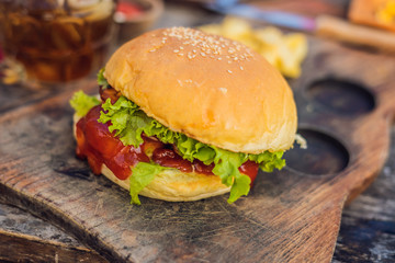 Closeup of fresh burger with French fries on wooden table with bowls of tomato sauce. lifestyle food