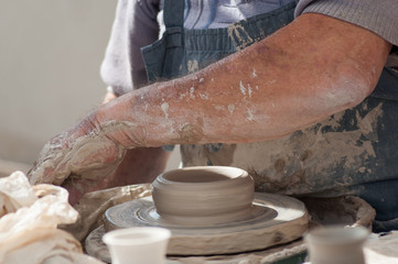 closeup of hands of old man making clay pottery in outdoor