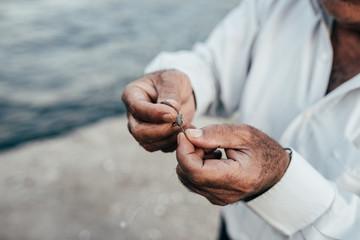 Hands preparing plummet for fishing