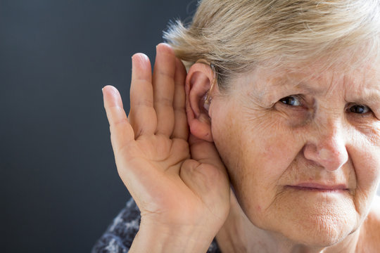 Elderly woman with hearing aid on grey background. Age related health problem.