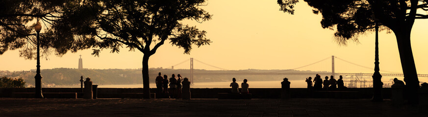 Beautiful panoramic image of silhouettes looking at the Ponte 25 de Abril bridge and the Sanctuary of Christ the King (Cristo Rei) at sunset from the Sao Jorge Castle in Lisbon, Portugal