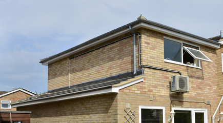 Residential home in the UK with an Air conditioning unit on the side
