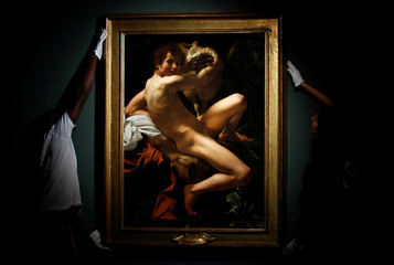 "Workers install the painting entitled ""Saint John the Baptist (Youth With a Ram)"" by Italian master Caravaggio at he Musee Jacquemart-Andre in Paris"