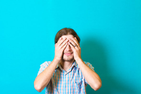 Portrait of a young man covering his eyes with hands