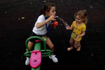 A girl blows soap bubbles as she plays with her sister at a park in Bangkok