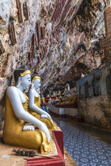 Religious carvings on limestone rock in sacred Kaw Goon cave near Hpa-An in Myanmar (Burma)