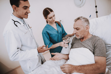 Doctor and Nurse with Sick Patient in Hospital.