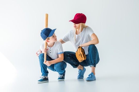 mommy and son squatting with baseball bat and glove on white and looking at each other