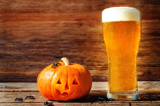 Glass of cold light beer with pumpkin on a wood background for Halloween