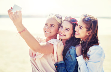 summer vacation, holidays, travel, technology and people concept- group of smiling young women taking selfie with smartphone on beach
