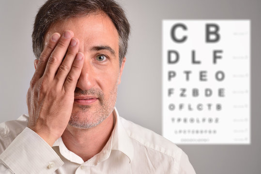 Middle-aged man covering an eye for optical revision letter chart