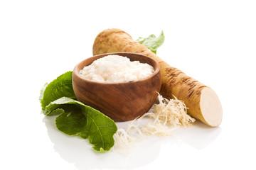 Fresh grated horseradish roots on white.