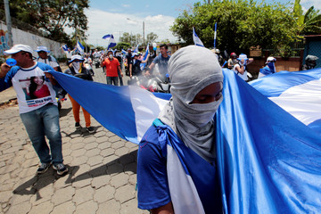 Anti-government protesters hold a big national flag during a protest against Nicaraguan President Daniel Ortega's government in Managua
