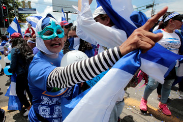 An anti-government protester shouts slogans to riot police during a protest against Nicaraguan President Daniel Ortega's government in Managua