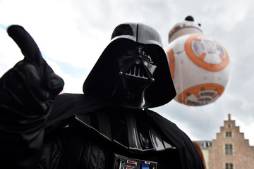 A giant balloon of BB-8 floats behind a participant wearing Darth Vader costume during the Balloon Day Parade in Brussels