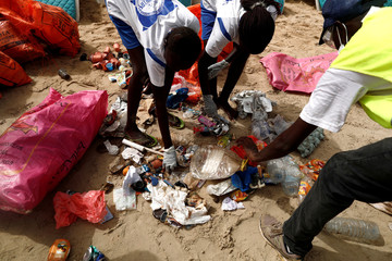 Volunteers from Zero Waste association clean up and remove waste from a beach during the World Cleanup Day in Dakar