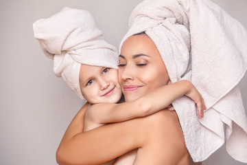 Woman young adult with daughter after shower in fresh towels hugging on isolated background