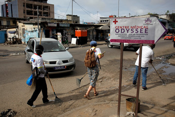 Volunteers clean a street of Treichville during the world clean up day in Abidjan