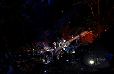 Rescuers take part in a search for fellow miners buried in the rubble of a bunkhouse after a landslide caused by Typhoon Mangkhut at a small-scale mining camp in Itogon