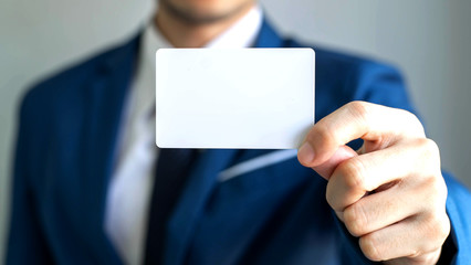 businessman  holding and showing empty business card or name card - business concept