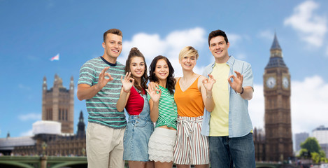 travel, tourism and summer holidays concept - group of happy smiling friends showing ok hand sign over houses of parliament in london city background