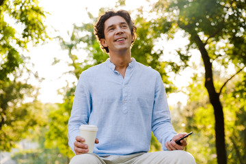 Cheerful young casual man using mobile phone