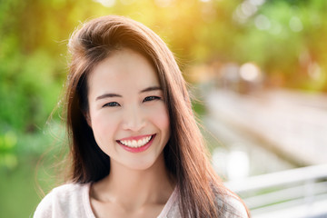 Asian teenage girl with long hair that is well maintained. Skin looks beautiful. Have a bright smile. She takes care of her teeth and mouth. So make confident Not in the state of depression.