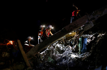 Rescuers take part in a search for miners buried at the rubble of a bunkhouse after a landslide caused by Typhoon Mangkhut at a small-scale mining camp in Itogon