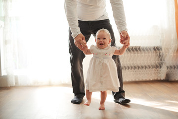 little daughter first steps with her father