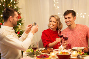 holidays and celebration concept - happy man photographing his friends at christmas dinner