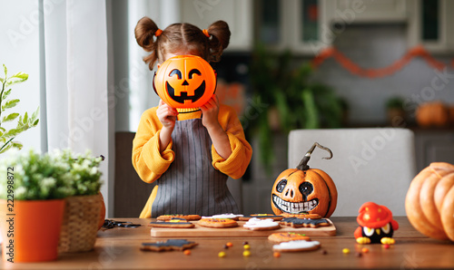 happy child girl in costumes of pumpkins are preparing for  holiday Halloween.