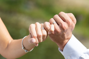 Married couple holding hands and showing wedding rings