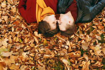 Top view Portrait of young couple in love woman, man with closed eyes facing each other blowing lips for kiss lying on fallen leaves in autumn city park outdoors. Love relationship family lifestyle.