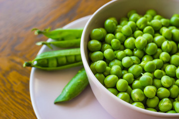 pink bowl with green peas and three pea pods lie near