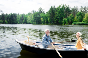 Calm rowing. Calm active pensioners enjoying the nature and feeling good while rowing the boat