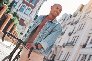 Pastime. Young guy walking on city street with bicycle looking aside smiling joyful close-up