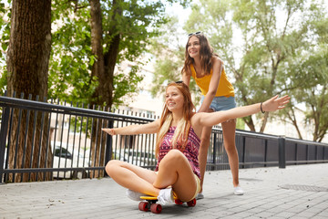 friendship, leisure and people concept - happy teenage girls or friends riding skateboard on city street in summer