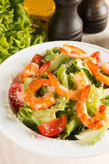 Fresh Caesar shrimp salad with delicious prawns, ruccola, spinach, cabbage, arugula, egg, parmesan and cherry tomato on wooden background. Oil, salt and pepper. Healthy and diet food concept.