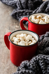 Christmas cocoa with marshmallow in mug on wooden table.