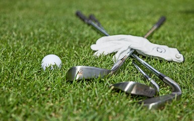 Golf Glove, Ball and Clubs on Golf Course