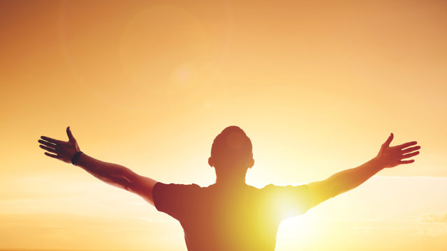 Young man standing outstretched at sunset. Bright solar glow and sky