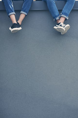 cropped view of couple in jeans and sneakers sitting on grey wall