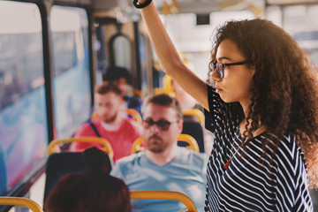 Serious young curly girl standing in a bus full of people.