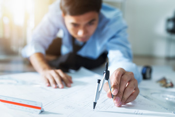 Close up of engineer Hand Drawing Plan a construction project with Pencil compass in office