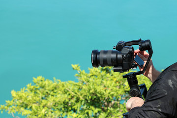 Photographer holding  the Camera Gimbal Stabilizer on top of the mountain